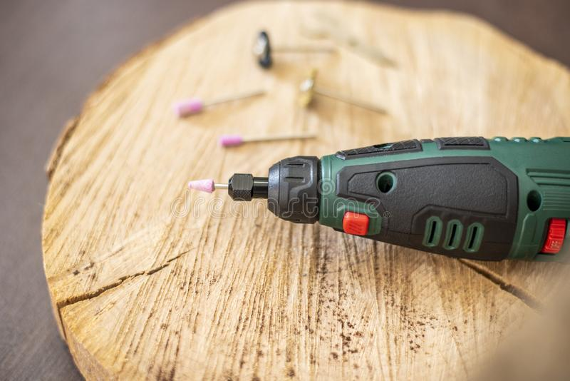 Strumento rotatorio del trapano con gli accessori, teste dello strumento di Dremel Multi strumento sulla tavola di legno nell'off immagini stock