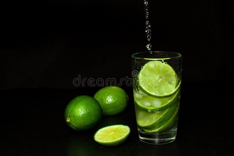 Strumień nalewa w szkło zimny napój z lodowymi i świeżymi dojrzałymi plasterek zieleni wapno na czarnym tle zdjęcie stock