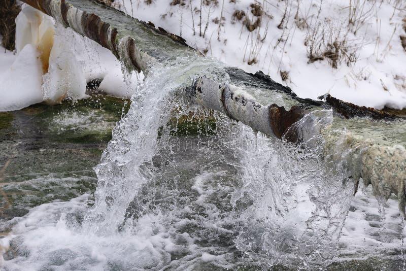 Strumień od jeziora nalewa z korodującej drymby w zimie zdjęcia royalty free