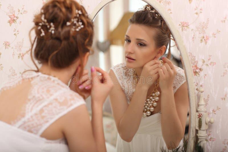 Strumpfbänder und Strümpfe Schöne junge Braut im weißen Hochzeitskleid zuhause Luxuty modellieren das betrachten des Spiegels und lizenzfreies stockfoto