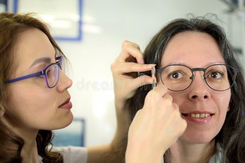 Struttura adattantesi di vetro dell'occhio del giovane paziente grazioso della donna con l'ottico dell'optometrista dell'oftalmol immagine stock libera da diritti