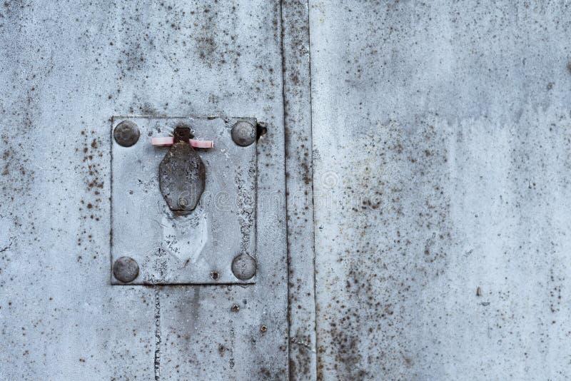 Struttura arrugginita del metallo con il buco della serratura, i graffi e le crepe coperti Tracce della pittura Colori blu, bianc fotografie stock