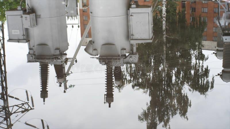 Struttura bagnata della strada asfaltata con le pozze e la riflessione di interramento del commutatore in  Pagina Asfalto bagnato fotografia stock libera da diritti