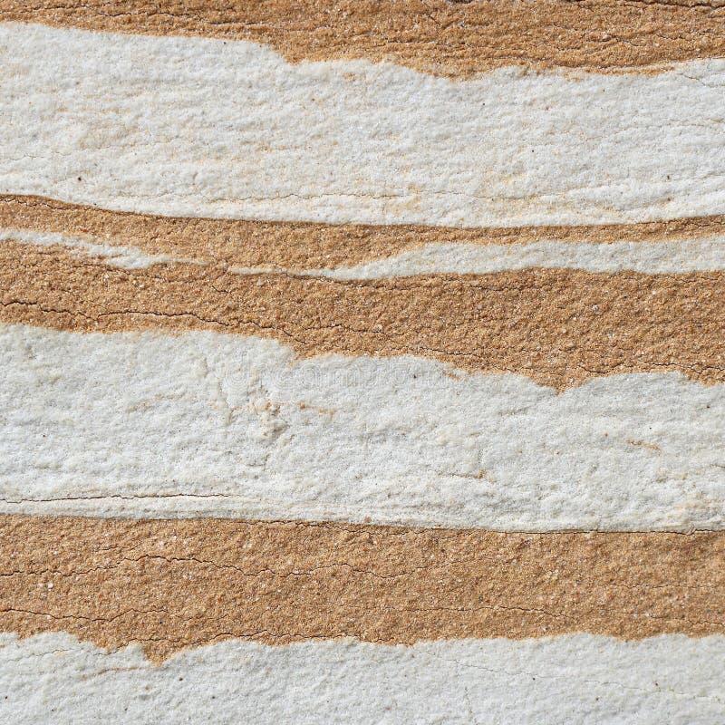 Struttura bianco-gialla astratta della parete di pietra di strati fotografia stock libera da diritti