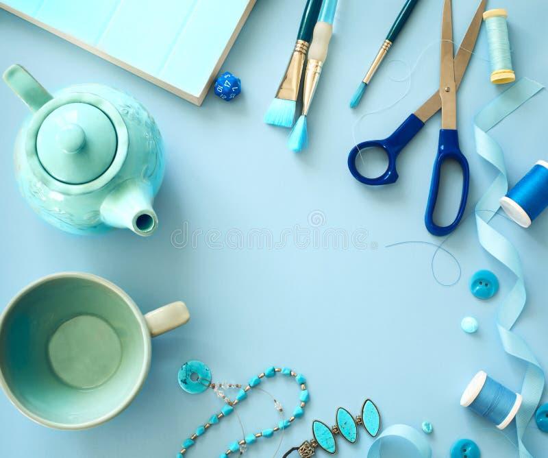 Struttura blu degli oggetti e degli accessori di colore di disposizione piana su fondo blu-chiaro immagini stock libere da diritti