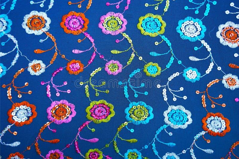 Struttura blu del tessuto con ricamo e gli zecchini floreali immagine stock libera da diritti