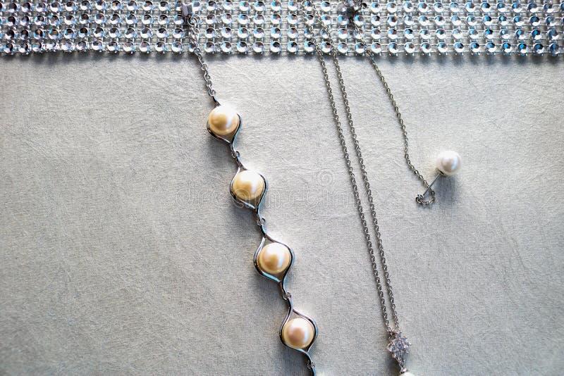 Struttura con i gioielli della perla, perle, catene d'argento, cristalli delle pietre preziose, diamanti, diamanti su un fondo gr immagini stock