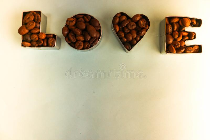 Struttura con l'amore di parola per l'iscrizione di San Valentino fatta dal fondo aromatico marrone selezionato dei fagioli del c fotografia stock libera da diritti