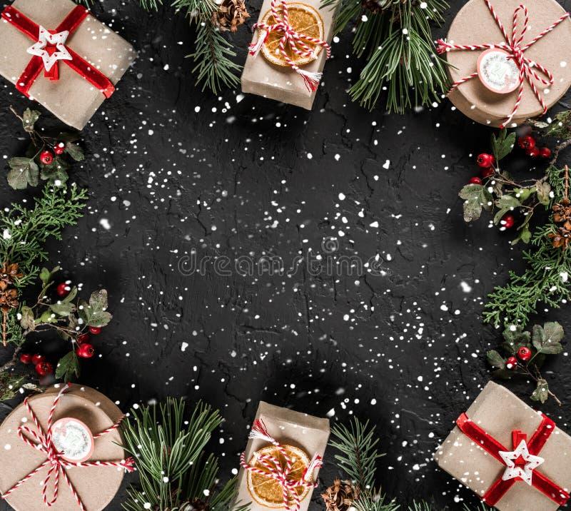 Struttura creativa della disposizione fatta dei rami dell'albero di Natale, pigne, regali su fondo scuro Tema del nuovo anno e di immagini stock