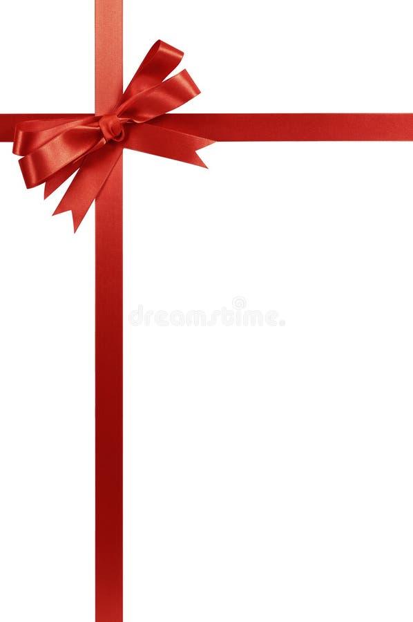 Struttura d'angolo verticale del confine del regalo dell'arco rosso del nastro isolata su bianco fotografia stock libera da diritti
