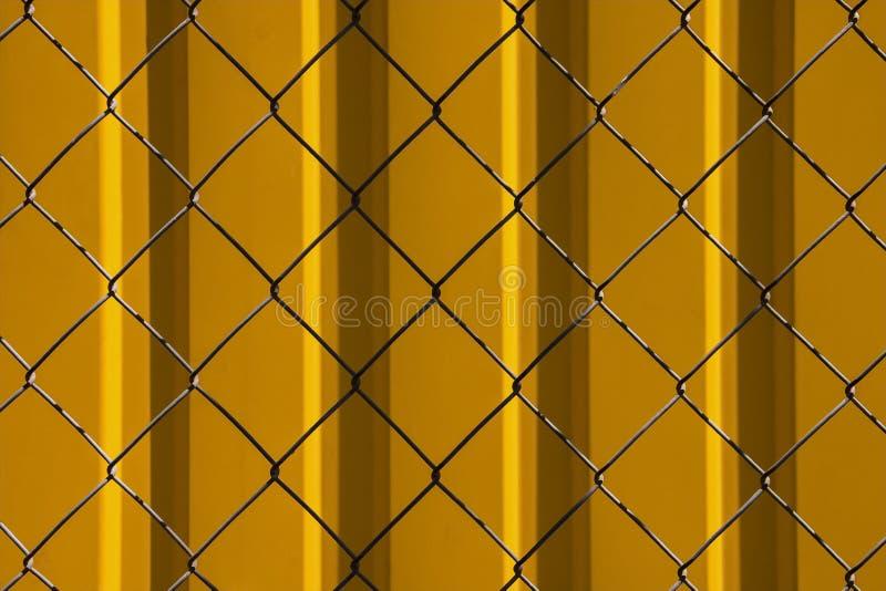 Struttura da una grata del metallo su un fondo del metallo giallo immagini stock