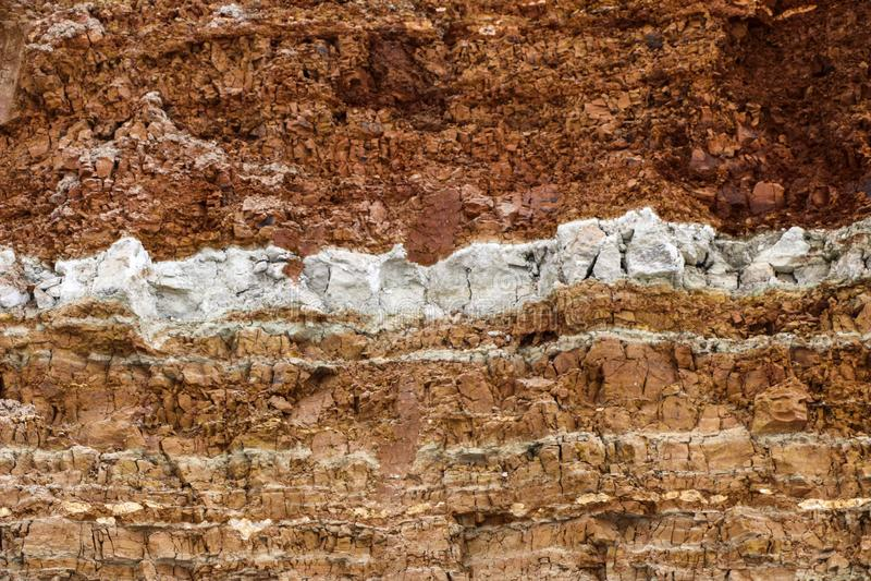 Struttura degli strati differenti di argilla sotterranei nella cava dell'argilla dopo lo studio geologico di suolo immagini stock