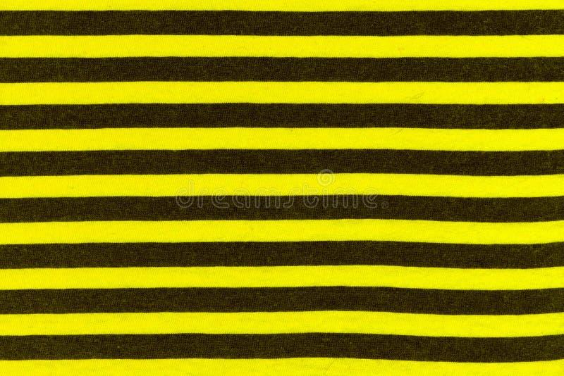 Struttura dei lavori o indumenti a maglia reali in bande nere e gialle, fondo del tessuto immagini stock