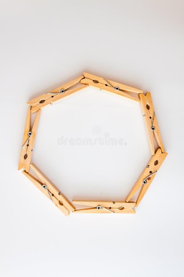 struttura del cerchio fatta delle mollette di legno su un fondo bianco Vista da sopra Copi lo spazio Il concetto di naturalezza e immagine stock libera da diritti