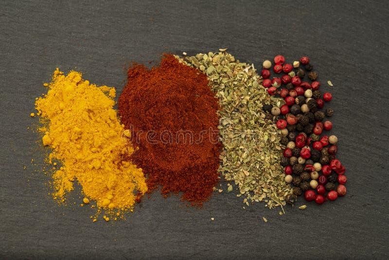 Struttura del fondo delle erbe che condiscono le spezie da curcuma, da peperone dolce, da basilico, da pepe nero, da peperone e d fotografia stock