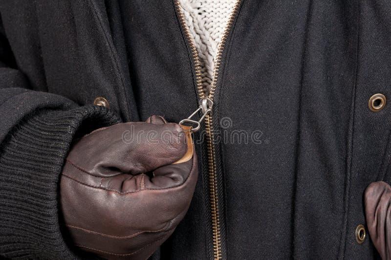 Struttura del primo piano della tenuta aperta del rivestimento della chiusura lampo con i guanti di cuoio fotografie stock