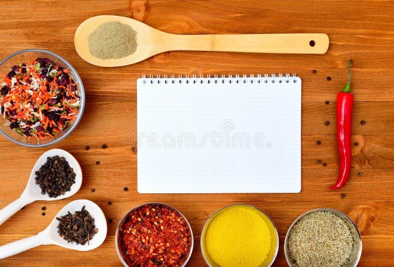 Struttura dell'alimento di Copyspace con le spezie della carta del blocco note e gli accessori di cottura immagini stock