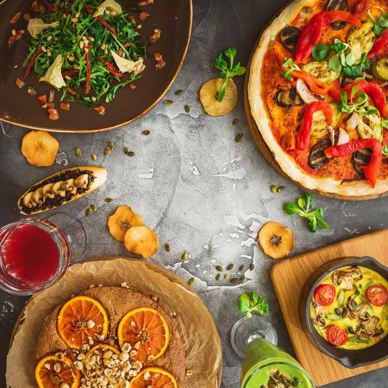 Struttura dell'alimento fatta di pizza con le bevande delle verdure, dell'insalata, della torta e della frutta su fondo scuro Dis fotografia stock
