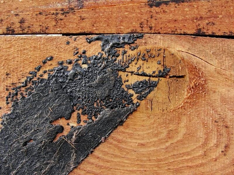Struttura struttura della parete di legno rossa delle plance, struttura rustica con le tracce di bitume coperte fotografia stock libera da diritti