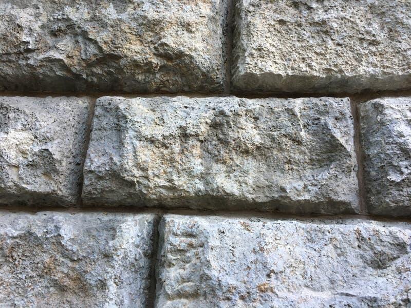 Struttura della parete di pietra con i grandi mattoni su monumento storico antico immagine stock