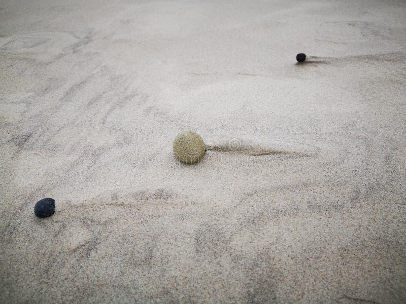 Struttura della sabbia sulla spiaggia con le piccole pietre Fondo immagini stock libere da diritti