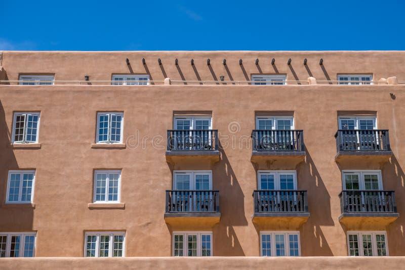 Struttura di Adobe con le file delle finestre e dei balconi fotografie stock