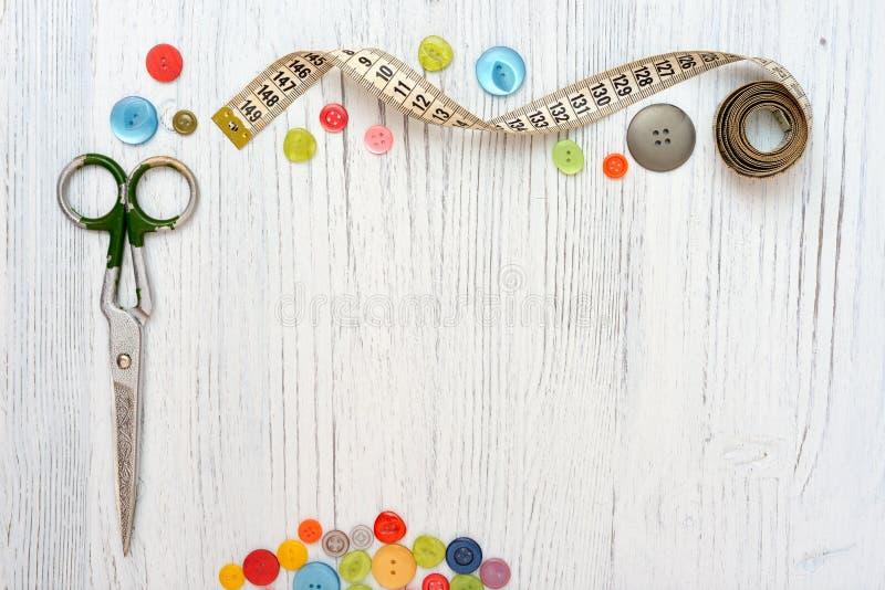 Struttura di Copyspace con gli strumenti e gli accessori di cucito su fondo di legno bianco immagini stock