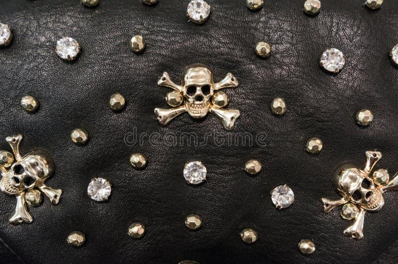 Struttura di cuoio nera con i crani del metallo fotografia stock