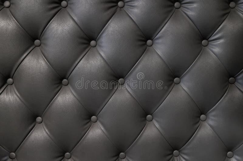 Struttura di cuoio nera elegante con i bottoni per il modello ed il fondo immagine stock