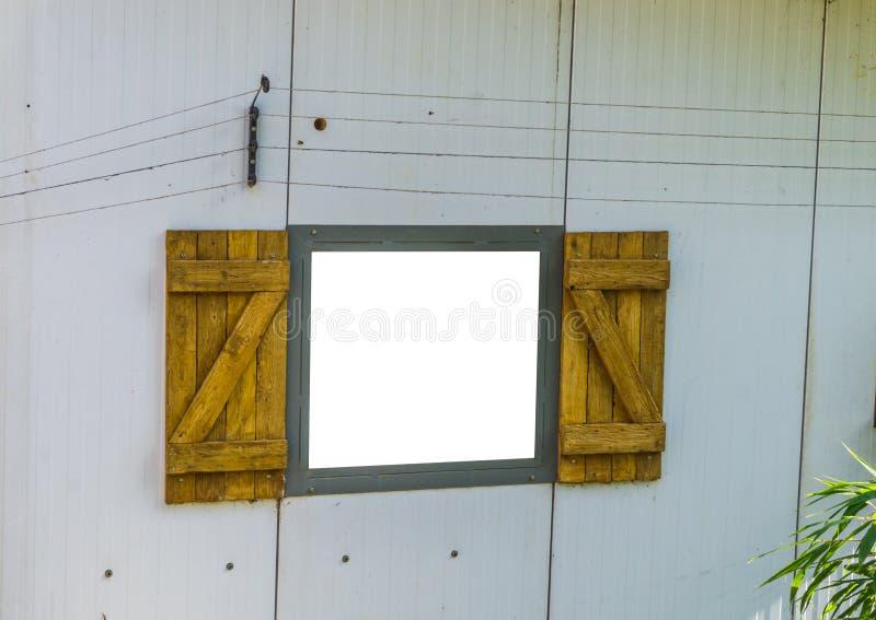 Struttura di finestra aperta tagliata ed isolata con la finestra bianca e classica con gli otturatori di legno immagini stock