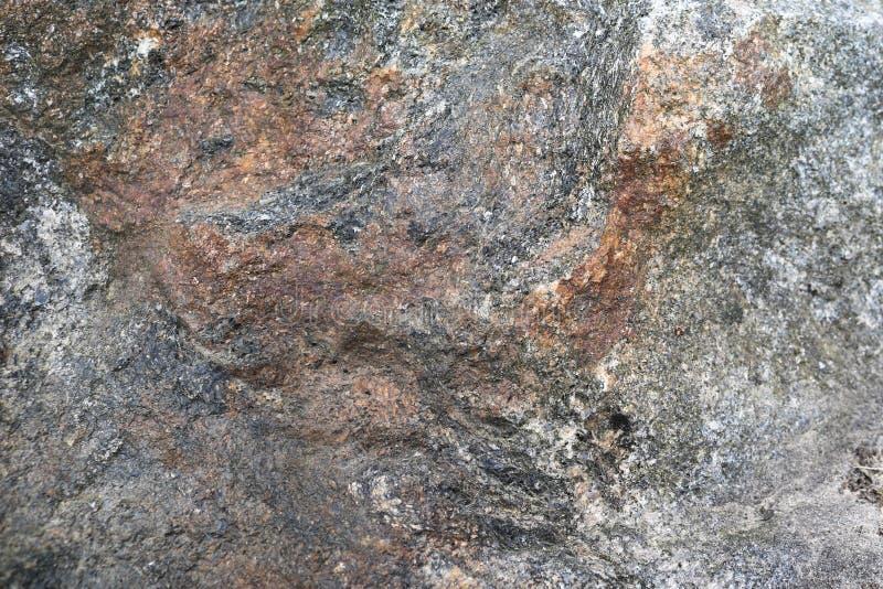 Struttura di grigio-Brown, di vecchia pietra solida colorata multi con le crepe, gli urti ed i modelli fotografie stock libere da diritti