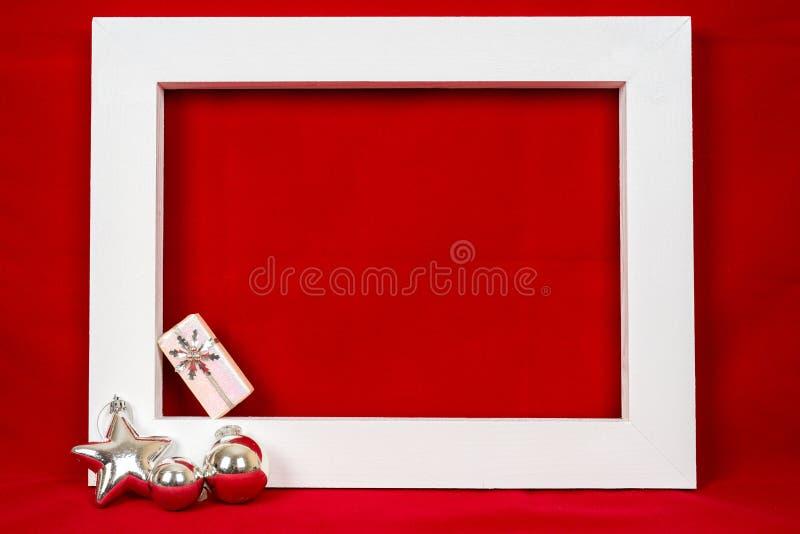 Struttura di legno bianca e un regalo di natale sopra un fondo rosso immagine stock