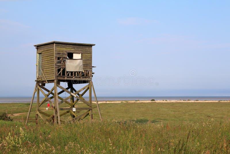 Struttura di legno del pellame che esamina fuori sopra le paludi di Essex Dengie verso il mare immagini stock libere da diritti