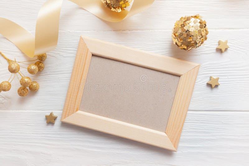 Struttura di legno leggera di Natale su un fondo di legno con il nastro ed i giocattoli dorati Disposizione piana, modello della  immagini stock