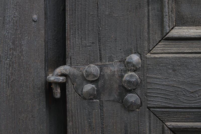 Struttura di legno reale con un elemento lavorato a mano del ferro Legno con il fondo del ferro Una porta di legno con una serrat fotografia stock libera da diritti