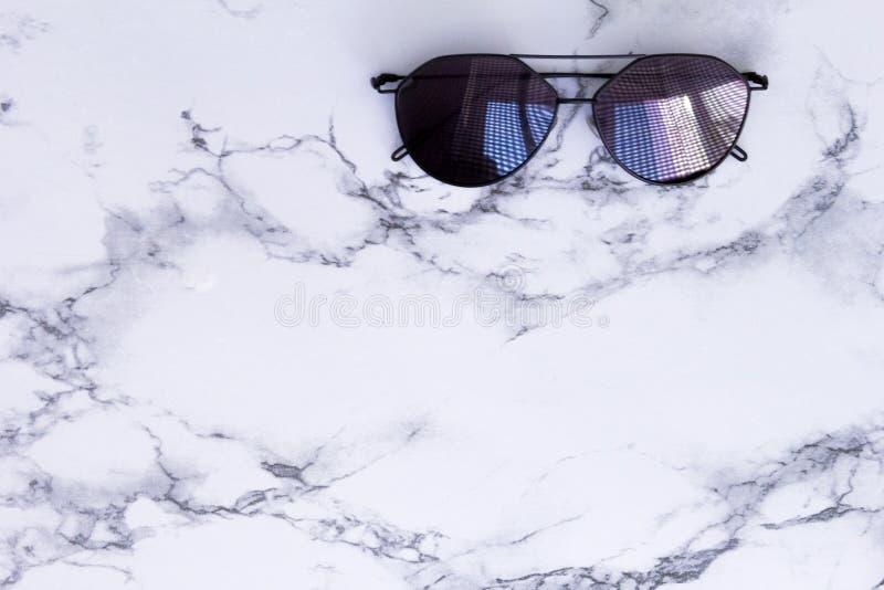 Struttura di marmo bianca con l'ombra nera degli occhiali da sole e fondo per il materiale illustrativo del modello di progettazi fotografia stock