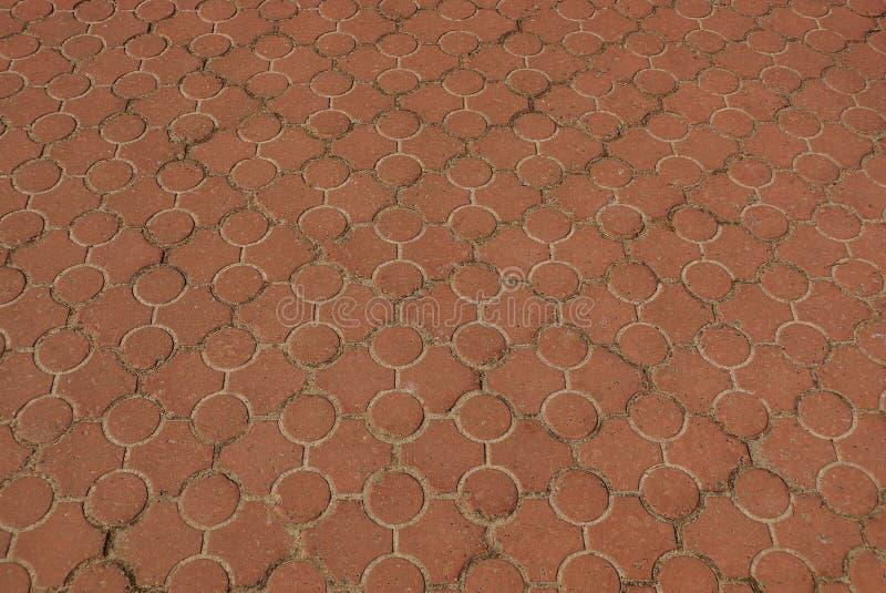 Struttura di pietra di Brown di pavimentazione delle mattonelle con un modello sulla strada fotografie stock libere da diritti