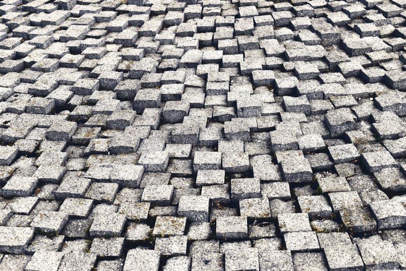 Struttura di pietra della pavimentazione Fondo della pavimentazione lapidato ciottolo del granito Fondo astratto di vecchio primo fotografia stock libera da diritti