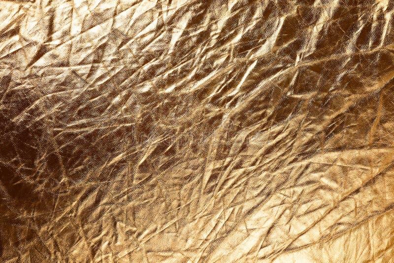 Struttura di tessuto metallizic dorato fotografia stock libera da diritti