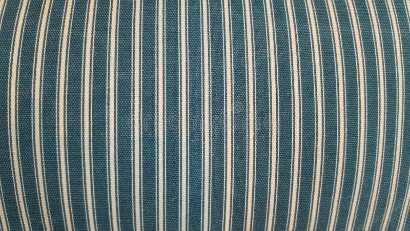 Struttura di un tessuto di un cuscino, sofà, letto, fondo Chiuda su, linee verticali barrate, blu e bianche fotografia stock libera da diritti