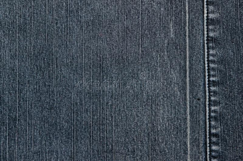 Struttura di un tessuto grigio del denim Due pezzi di tessuto cuciti insieme immagini stock libere da diritti