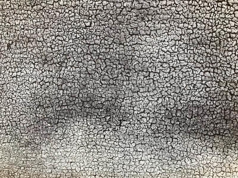 Struttura di vecchio muro di cemento dilapidato grigio nero con i pezzi di vecchia pittura esfoliata misera con le crepe, vene fotografia stock