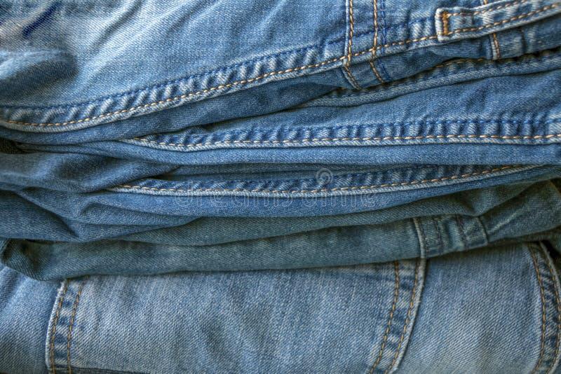 Struttura, fondo del mucchio dei pantaloni blu del denim immagine stock