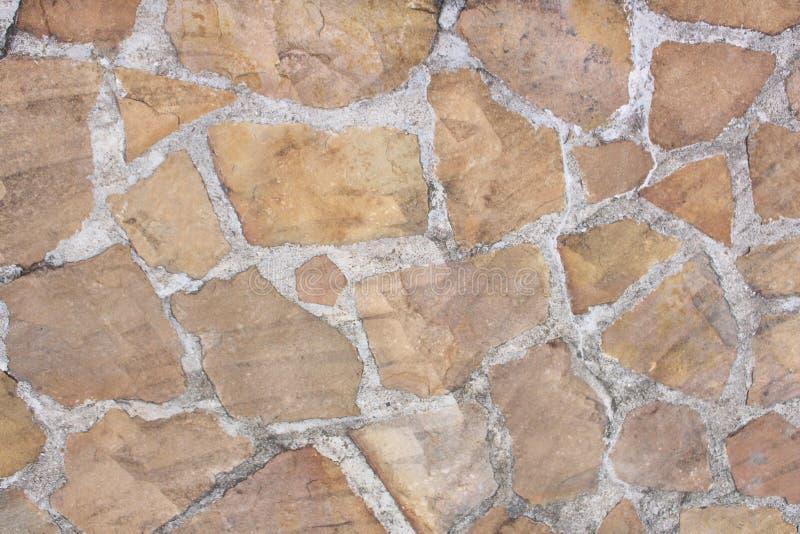 Struttura marrone chiaro della roccia della decorazione nel vecchio fondo dell'estratto del muro di cemento fotografie stock