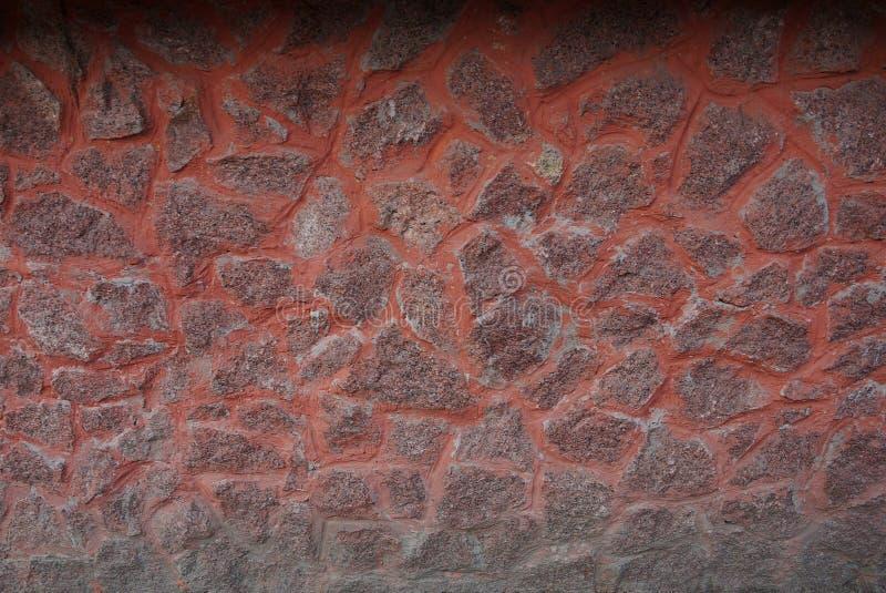 Struttura marrone-rosso della pietra del ciottolo della pietra in una parete del recinto fotografia stock libera da diritti