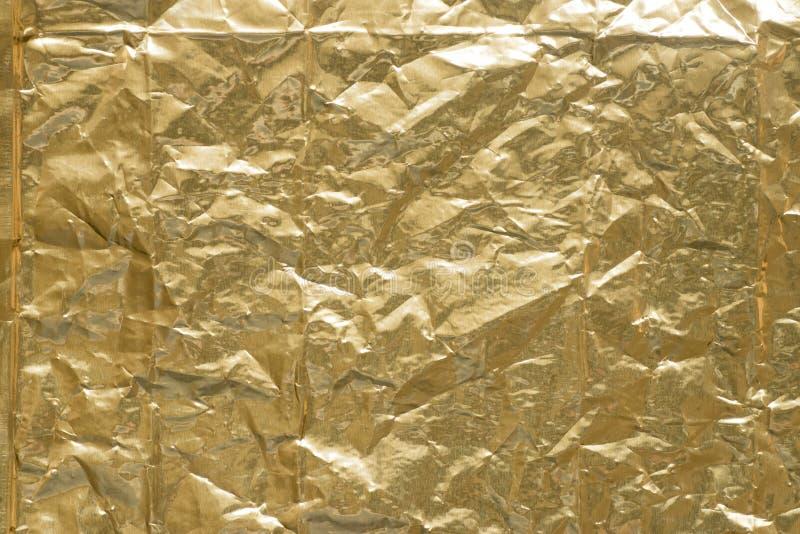 Struttura metallica del fondo della stagnola piegata oro immagini stock libere da diritti