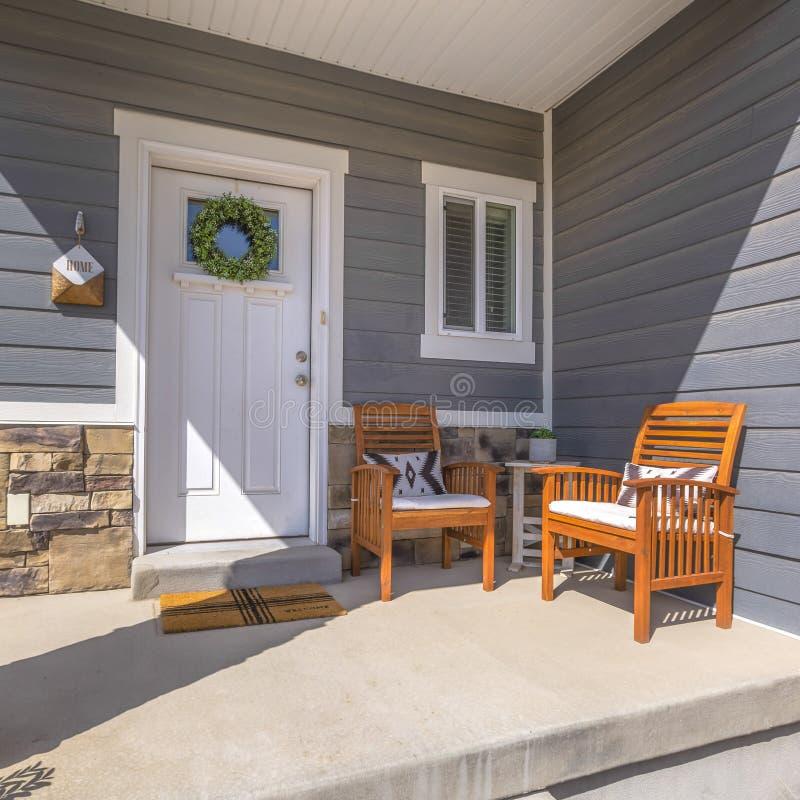 Struttura quadrata Facacde di una casa con mobilia sul portico soleggiato d'accoglienza fotografia stock libera da diritti