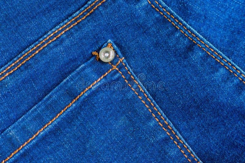 Struttura reale del fondo del tessuto del denim delle blue jeans tasca posteriore vuota con la cucitura giallo arancione ed il ri fotografie stock libere da diritti