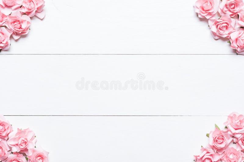 Struttura rosa delle rose sulla tavola di legno bianca con copyspace vuoto fotografia stock
