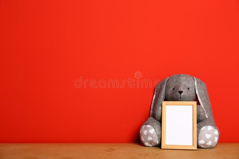 Struttura vuota della foto ed e morbido sulla tavola di legno contro fondo rosso, spazio per testo Interno della stanza di bambin fotografia stock